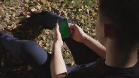 Homem que guarda o telefone esperto preto com a tela verde no fundo da rua da cidade no dia ensolarado Tela grande Rua de Cobblet video estoque