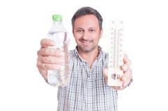 Homem que guarda o termômetro e a garrafa de água fria imagem de stock