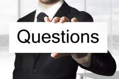 Homem que guarda perguntas do sinal Fotografia de Stock