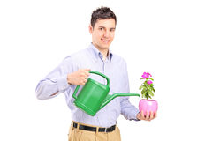 Homem que guarda a planta e uma lata molhando Fotos de Stock Royalty Free