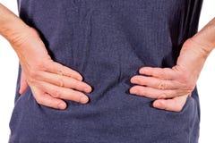 Homem que guarda seu lombo inflamado doloroso no fundo branco Cuidados médicos e medicina Sofrimento da dor nas costas fotografia de stock royalty free