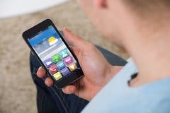 Homem que guarda Smartphone com ícones coloridos da aplicação Imagem de Stock Royalty Free