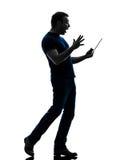 Homem que guarda tabuleta digital a silhueta surpreendida Fotografia de Stock