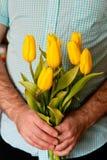 Homem que guarda tulipas amarelas Dia de mães, conceito do dia das mulheres Fotografia de Stock Royalty Free