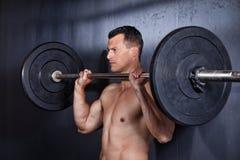 Homem que guarda um barbell que faz um exercício da aptidão Foto de Stock