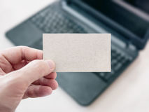 Homem que guarda um cartão vazio do cartão e que usa o portátil Imagens de Stock Royalty Free
