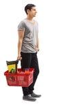 Homem que guarda um cesto de compras que espera na linha fotografia de stock royalty free
