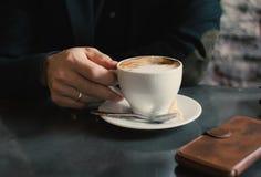 Homem que guarda um copo do cappuccino foto de stock royalty free