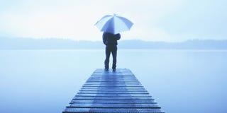 Homem que guarda um guarda-chuva em um molhe pelo conceito tranquilo do lago Fotografia de Stock