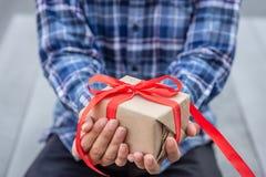 Homem que guarda um presente do ofício imagem de stock royalty free