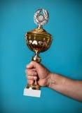 Homem que guarda um troféu dourado Fotos de Stock Royalty Free
