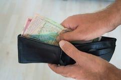 Homem que guarda uma carteira com dinares para dentro Foto de Stock Royalty Free