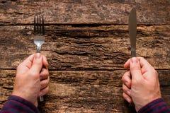 Homem que guarda uma faca e uma forquilha Foto de Stock Royalty Free
