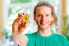Homem que guarda uma moeda física do bitcoin imagens de stock royalty free