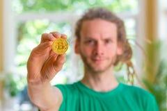 Homem que guarda uma moeda física do bitcoin foto de stock royalty free