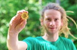 Homem que guarda uma moeda física do bitcoin imagens de stock