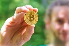 Homem que guarda uma moeda física do bitcoin imagem de stock