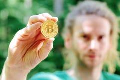 Homem que guarda uma moeda física do bitcoin fotos de stock royalty free