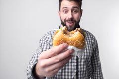 Homem que guarda uma parte de Hamburger o estudante come o fast food alimento não útil indivíduo muito com fome imagem de stock