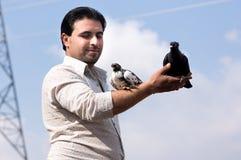 Homem que guarda uma pomba e um pombo Fotos de Stock