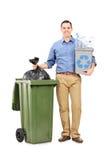 Homem que guarda uma reciclagem por um balde do lixo Imagens de Stock Royalty Free