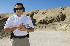 Homem que guardara a arma da mão na escala de acendimento Fotografia de Stock Royalty Free