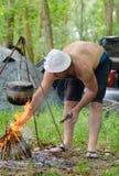 Homem que ilumina um fogo de cozimento ao acampar foto de stock
