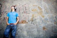 Homem que inclina-se de encontro à parede com grafittis Fotos de Stock Royalty Free