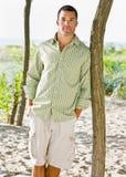 Homem que inclina-se na árvore na praia fotos de stock