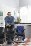 Homem que inclina-se na cadeira no cabeleireiro Imagem de Stock