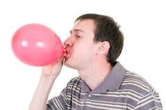 Homem que infla o balão vermelho Fotografia de Stock Royalty Free