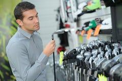 Homem que inspeciona clubes de golfe fotos de stock royalty free