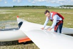 Homem que inspeciona o planador da asa Imagens de Stock Royalty Free