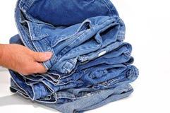 Homem que inspeciona um par de calças de brim Imagem de Stock Royalty Free
