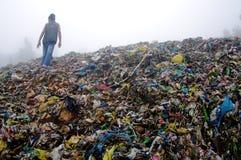 Homem que inspeciona uma montanha do lixo imagem de stock royalty free