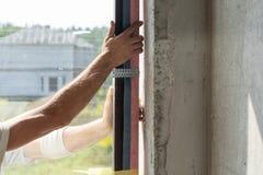Homem que instala o quadro de janela plástico na casa nova foto de stock royalty free