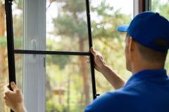 Homem que instala a tela de malha do inseto para proteger a sala do mosquito fotos de stock royalty free