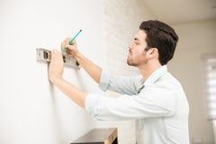 Homem que instala uma prateleira em casa Imagem de Stock