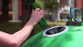 Homem que joga afastado a garrafa vazia, de vidro no escaninho de reciclagem video estoque