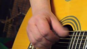 Homem que joga ascendente próximo da guitarra video estoque