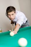 Homem que joga bilhar no clube Foto de Stock