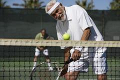Homem que joga dobros no campo de tênis Fotos de Stock Royalty Free