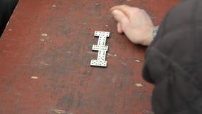 Homem que joga dominós no tampo da mesa áspero filme