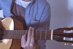 Homem que joga a guitarra acústica Fotografia de Stock Royalty Free