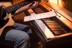 Homem que joga a guitarra acústica e o close-up do piano, notas de gravação imagem de stock