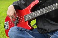 Homem que joga a guitarra baixa fotografia de stock