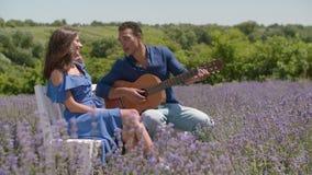 Homem que joga a guitarra e que canta à mulher na natureza video estoque