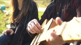 Homem que joga a guitarra para a amiga outdoor rom?ntico filme