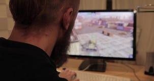 Homem que joga jogos de computador em um computador doméstico Vista traseira filme