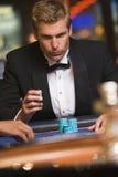 Homem que joga na tabela da roleta no casino fotografia de stock